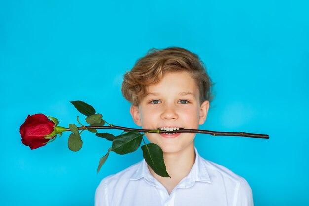 Nastoletnia chłopiec mienia czerwieni róża jego usta i ono uśmiecha się na błękitnym tle. skopiuj miejsce
