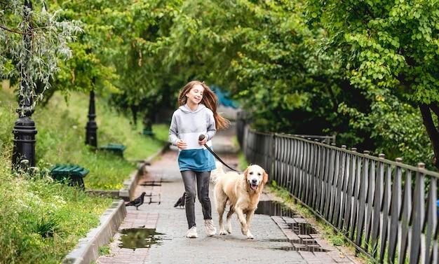 Nastoletnia dziewczyna biegnie z psem golden retriever w parku po deszczu