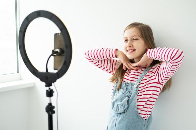 Nastoletnia dziewczyna blogerka mediów społecznościowych nagrywa przemówienie wideo patrząc na smartfona na statywie z pierścieniem świetlnym.