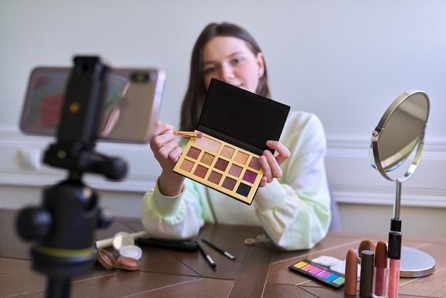 Nastoletnia dziewczyna, blogerka piękności kręci wideo na blogu kanału, pokazując cień do powiek. mówienie i pokazywanie makijażu oraz niewidzialny naturalny makijaż. piękno, technologia, komunikacja nastolatki online