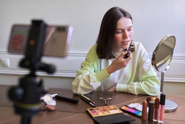 Nastoletnia dziewczyna, blogerka zajmująca się urodą, kręci wideo na blogu kanału, pokazując błyszczyk. opowiadanie i pokazywanie makijażu, którego używa i robi niewidoczny naturalny makijaż. piękno, technologia, komunikacja nastolatki online