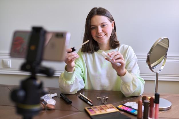 Nastoletnia dziewczyna, blogerka zajmująca się urodą, kręci wideo na blogu kanału, pokazując błyszczyk. opowiadanie i pokazywanie makijażu, którego używa i robi niewidoczny naturalny makijaż. uroda, technologia, komunikacja nastolatków online