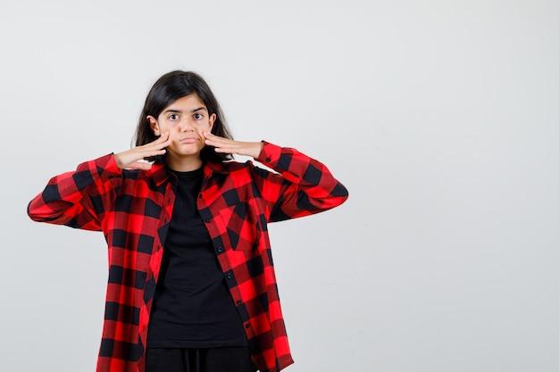 Nastoletnia dziewczyna ciągnie skórę w t-shirt, koszulę w kratkę i wygląda na skoncentrowaną. przedni widok.