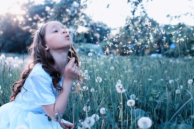 Nastoletnia dziewczyna dmuchająca nasionami z mniszka lekarskiego w wiosennym parku
