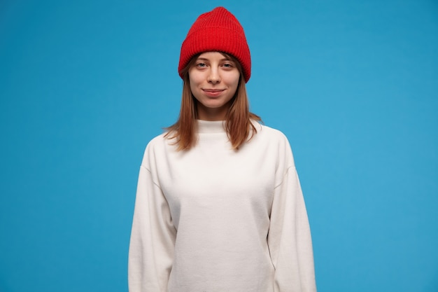 Nastoletnia dziewczyna, fajnie wyglądająca kobieta z brunetką. na sobie biały sweter i czerwoną czapkę. ludzie i koncepcja emocjonalna.