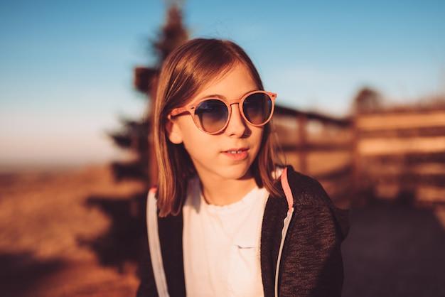 Nastoletnia dziewczyna jest ubranym okularów przeciwsłonecznych siedzieć plenerowy przy zmierzchem