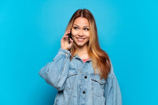 Nastoletnia dziewczyna korzystająca z telefonu komórkowego na białym tle, patrząc w bok i uśmiechnięta