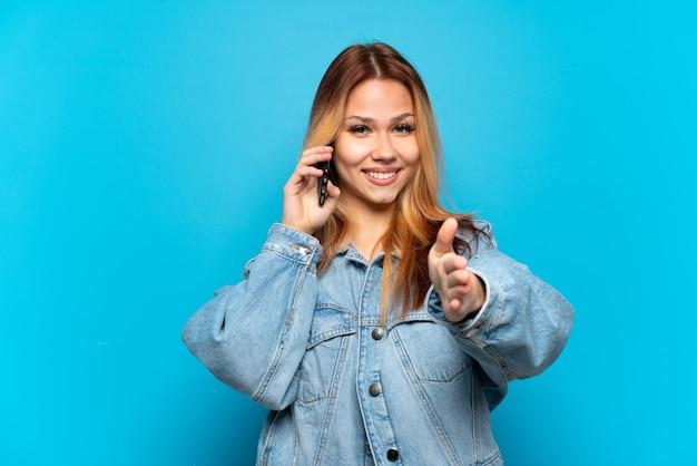 Nastoletnia dziewczyna korzystająca z telefonu komórkowego na białym tle, ściskając ręce, aby zamknąć dobrą ofertę
