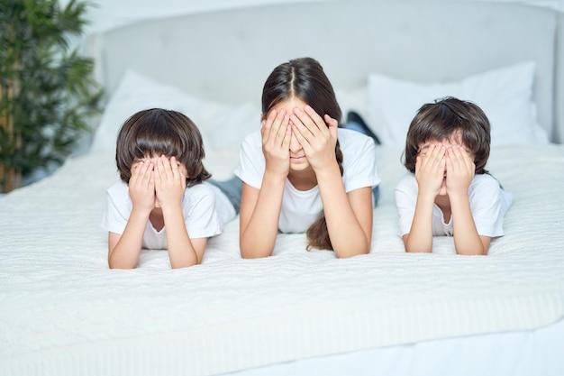 Nastoletnia dziewczyna latynoska i dwóch małych chłopców leżących na łóżku z zamkniętymi oczami. siostra spędza czas ze swoimi uroczymi braćmi, bawiąc się w chowanego w domu. koncepcja szczęśliwe dzieci