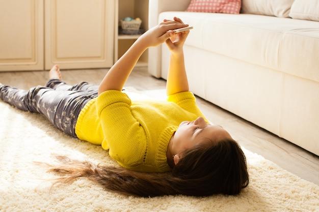 Nastoletnia dziewczyna leży na podłodze i patrzy na smartfona