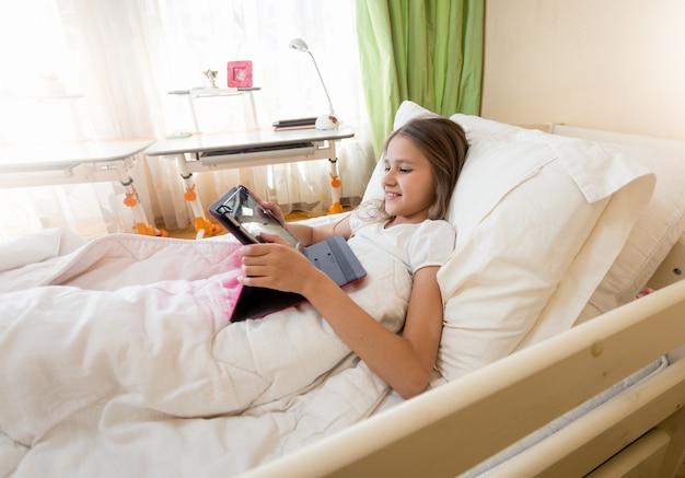 Nastoletnia dziewczyna leży rano w łóżku i korzysta z cyfrowego tabletu