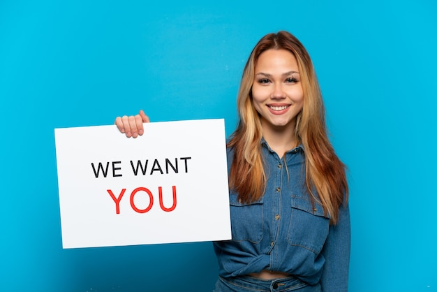 Nastoletnia dziewczyna na odosobnionym niebieskim tle trzyma deskę we want you ze szczęśliwym wyrazem twarzy