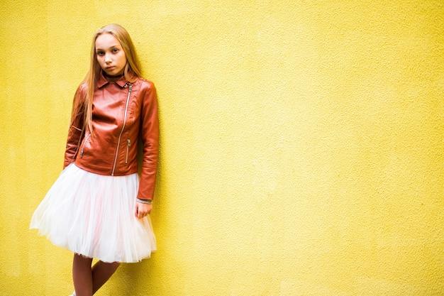 Nastoletnia dziewczyna na żółtym ściennym tle