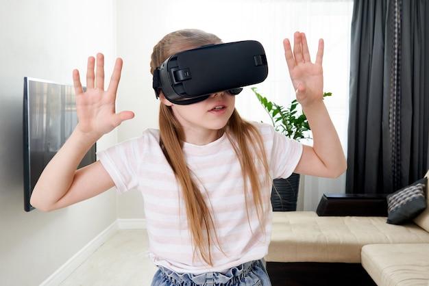 Nastoletnia dziewczyna nosi słuchawki wirtualnej rzeczywistości i gra, vr box. technologia, nowa generacja, koncepcja postępu. dziewczyna próbuje dotykać obiektów w wirtualnej rzeczywistości.