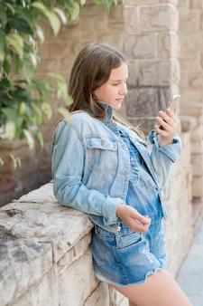 Nastoletnia dziewczyna opiera na ścianie patrzeje telefon komórkowego