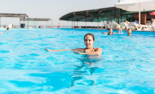 Nastoletnia dziewczyna pływa w krystalicznie czystej wodzie basenu podczas wakacji w ciepłym tropikalnym kraju
