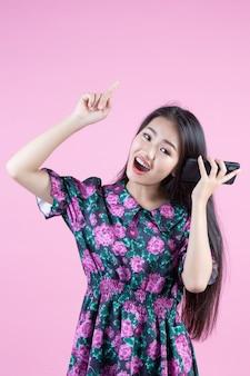 Nastoletnia dziewczyna pokazuje telefon i twarzowe emocje