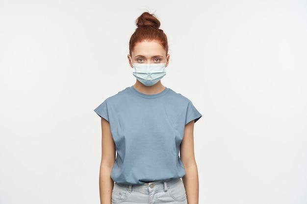 Nastoletnia dziewczyna, poważnie wyglądająca kobieta o rudych włosach zebranych w kok. ubrana w niebieską koszulkę, dżinsy i ochronną maskę na twarz. pojedynczo na białej ścianie