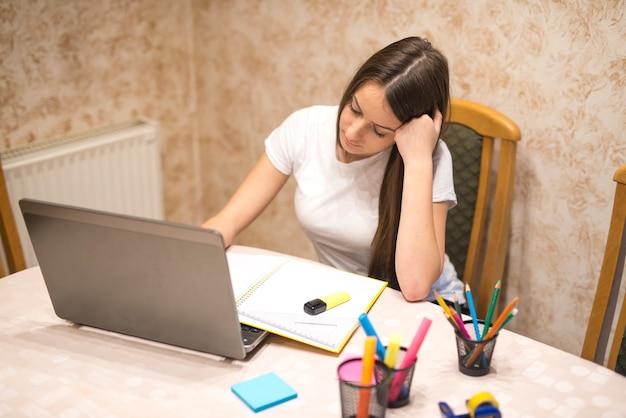 Nastoletnia dziewczyna przygotowuje się do zajęć przy użyciu swojego komputera przenośnego