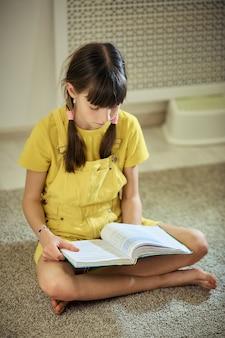 Nastoletnia dziewczyna robi pracie domowej siedzi na dywanie w jej pokoju