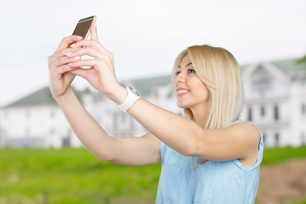 Nastoletnia dziewczyna robi selfie fotografii z mądrze telefonem
