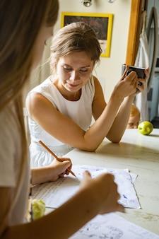 Nastoletnia dziewczyna rysująca obrazek na kartce papieru lub robiąca notatki używa pióra matki rozmawiającej pijąc herbatę