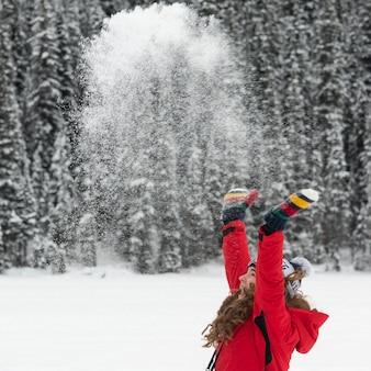 Nastoletnia dziewczyna rzucający śnieg w powietrzu, park narodowy banff, alberta, kanada