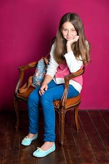 Nastoletnia dziewczyna siedzi na fotelu na pomalowanym różowym tle ściany, uśmiechając się i czekając na coś