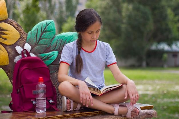 Nastoletnia dziewczyna siedzi na ławce w parku i czyta książkę powrót do koncepcji szkoły