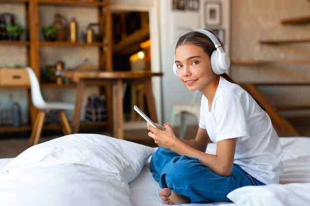 Nastoletnia dziewczyna siedzi na łóżku w słuchawkach z telefonem komórkowym i słucha muzy...