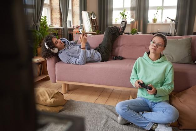 Nastoletnia dziewczyna siedzi na podłodze grając w grę wideo z chłopcem leżącym na kanapie grającym przez telefon w pokoju