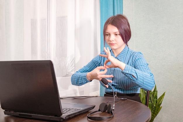 Nastoletnia dziewczyna siedzi przed laptopem i uczy się języka migowego, języka online dla osób niesłyszących i niemych.