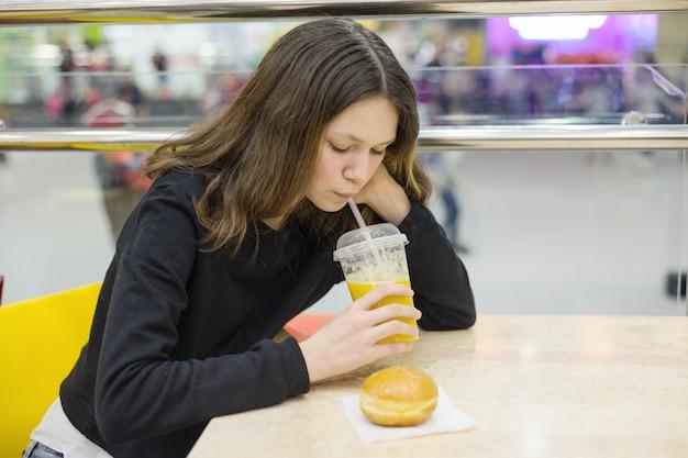 Nastoletnia dziewczyna siedzi przy stole, jedzenie ciasta i picie soku