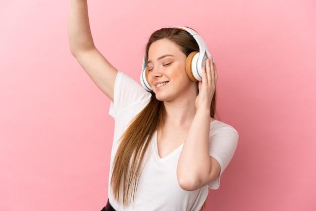 Nastoletnia dziewczyna słucha muzyki i tańca na odosobnionym różowym tle