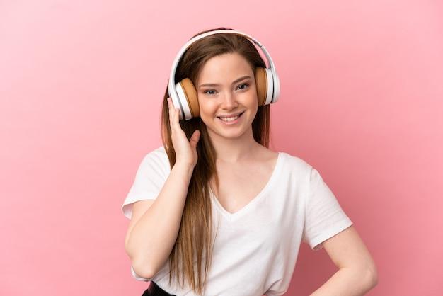 Nastoletnia dziewczyna słucha muzyki na odosobnionym różowym tle