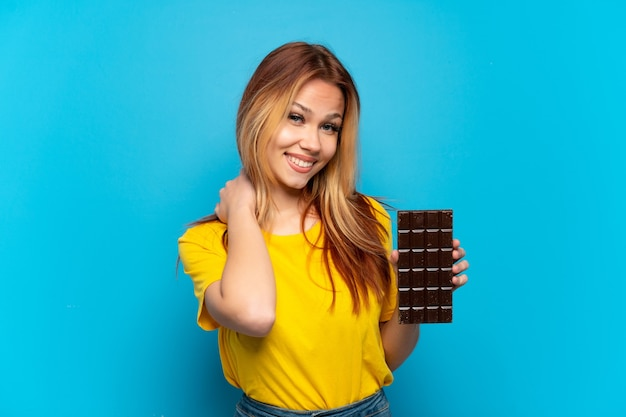 Nastoletnia dziewczyna śmiejąca się z czekoladą na odosobnionym niebieskim tle