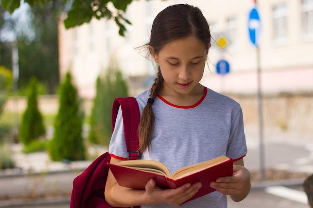 Nastoletnia dziewczyna stoi w pobliżu szkoły i czyta książkę powrót do koncepcji szkoły selektywne skupienie