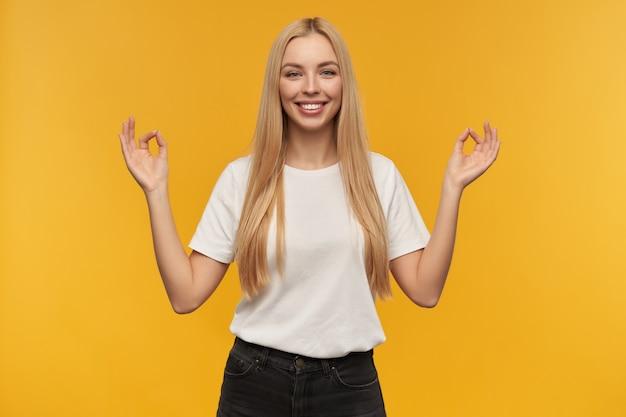 Nastoletnia dziewczyna, szczęśliwa patrząc kobieta o blond długich włosach. ubrana w białą koszulkę i dżinsy. uśmiecha się szeroko i pokazuje palcami znak mudry, patrząc w kamerę, odizolowane na pomarańczowym tle