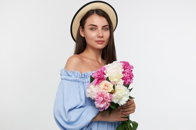 Nastoletnia dziewczyna, szczęśliwa patrząc kobieta z długimi włosami brunetka. nosi czapkę i niebieską ładną sukienkę. trzyma piękne kwiaty. oglądanie na białym tle nad białą ścianą