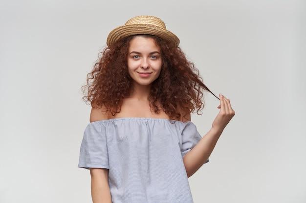 Nastoletnia dziewczyna, szczęśliwa patrząc kobieta z kręconymi rudymi włosami. na sobie bluzkę i kapelusz w paski z odkrytymi ramionami. bawiąc się kosmykiem włosów, uśmiechaj się. pojedynczo na białej ścianie
