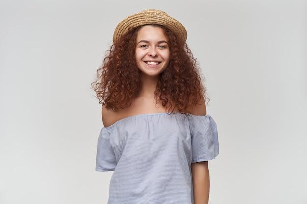 Nastoletnia dziewczyna, szczęśliwa patrząc kobieta z kręconymi rudymi włosami. na sobie bluzkę i kapelusz w paski z odkrytymi ramionami. miej duży, uroczy uśmiech. pojedynczo na białej ścianie