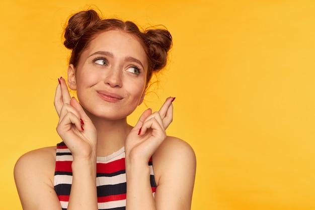Nastoletnia dziewczyna, szczęśliwie wyglądająca rudowłosa kobieta z dwoma bułeczkami. nosić podkoszulek w paski i trzymać kciuki. koncepcja emocjonalna. patrząc w prawo na miejsce kopiowania nad żółtą ścianą