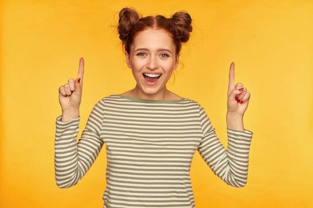 Nastoletnia dziewczyna, szczęśliwy patrząc rude włosy kobieta z dwoma bułeczkami. nosi sweter w paski i patrzy na aparat z uśmiechem, szczęśliwy, wskazując na miejsce na kopię, odizolowany na żółtej ścianie
