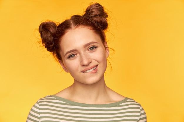 Nastoletnia dziewczyna, szczęśliwy patrząc rude włosy kobieta z dwoma bułeczkami. patrząc na ciebie zalotnie, przygryź wargę. na sobie sweter w paski na białym tle, zbliżenie na żółtej ścianie
