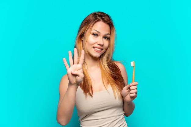 Nastoletnia dziewczyna szczotkuje zęby na odosobnionym niebieskim tle szczęśliwa i liczy cztery palcami