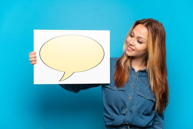 Nastoletnia dziewczyna trzyma afisz z ikoną dymka na odosobnionym niebieskim tle