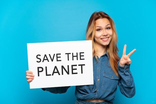 """Nastoletnia dziewczyna trzyma afisz z napisem """"uratuj planetę"""" i świętuje zwycięstwo na odosobnionym niebieskim tle"""