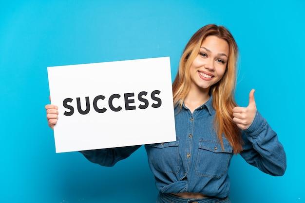 Nastoletnia dziewczyna trzyma afisz z tekstem sukces z kciukiem w górę na białym tle niebieski
