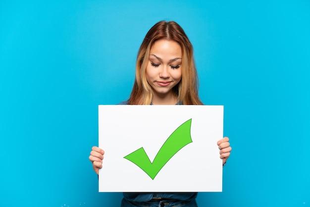 Nastoletnia dziewczyna trzyma afisz z tekstem zielona ikona znacznika wyboru na na białym tle niebieskim tle