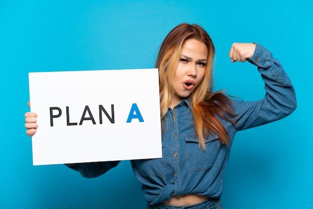 Nastoletnia dziewczyna trzyma afisz z wiadomością na odosobnionym niebieskim tle plan a robi mocny gest